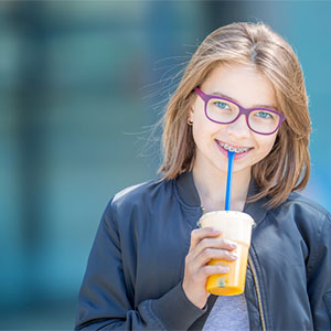 preteen girl with braces holding a drink